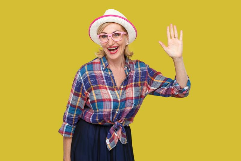 Portrait of surprised modern stylish mature woman in casual style with hat and eyeglasses standing waving her hand and looking at. Camera with toothy smile royalty free stock image
