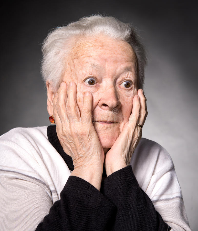 Portrait of surprised old woman. On a gray background royalty free stock images
