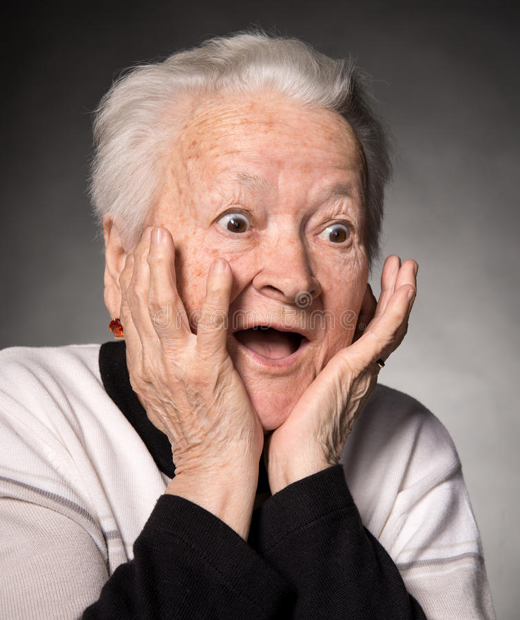 Portrait of surprised old woman. On a gray background royalty free stock photos