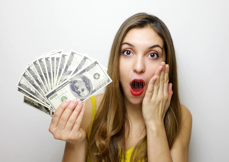 Portrait of a surprised pretty girl looking at camera with money banknotes in her hand isolated over white background royalty free stock photography