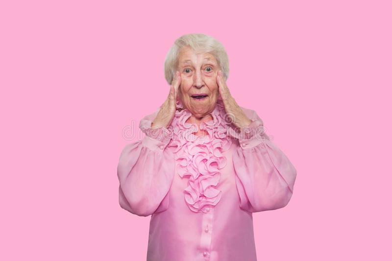 Portrait of a surprised senior woman over pink background. Portrait of a surprised senior woman over pink studio background royalty free stock images