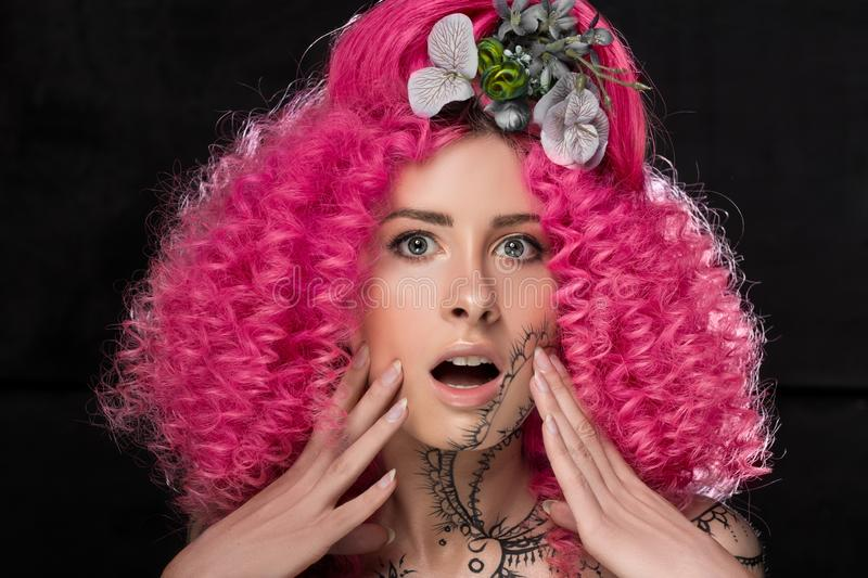 Portrait of surprised young attractive caucasian girl model with afro style curly bright pink hair, tattooed face and flowers stock photos