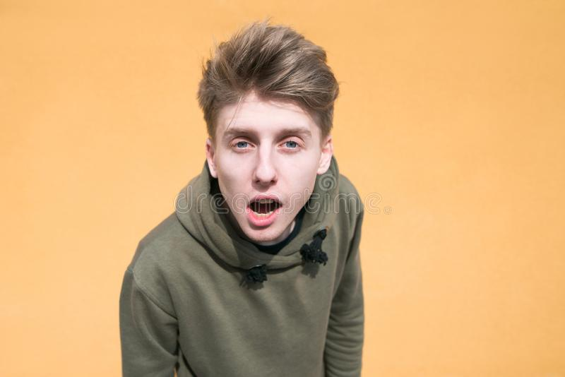 Portrait of a surprised young man on an orange background. A funny guy looking into the camera stock photography