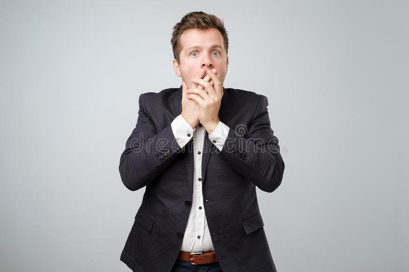 Portrait of surprised young men in suit covering his mouth by hand while standing isolated on grey wall. royalty free stock photography