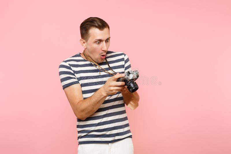 Portrait of surprised young photographer man wearing striped t-shirt take pictures on retro vintage photo camera stock photography