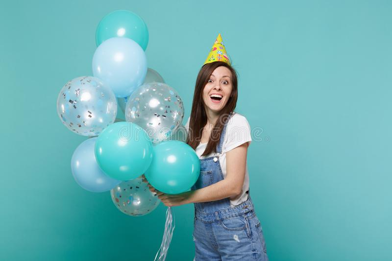 Portrait of surprised young woman in denim clothes, birthday hat celebrating, holding colorful air balloons isolated on. Blue turquoise wall background royalty free stock photos