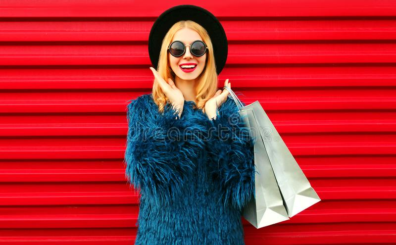 Portrait surprised young woman with shopping bags wearing blue faux fur coat, black round hat and sunglasses posing over red wall royalty free stock photos