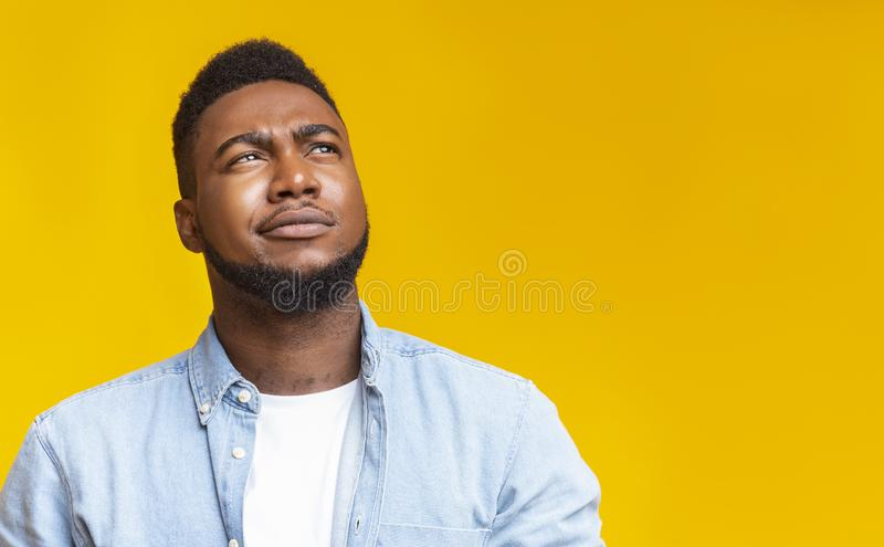 Portrait of suspicious black guy looking upwards at copy space stock images