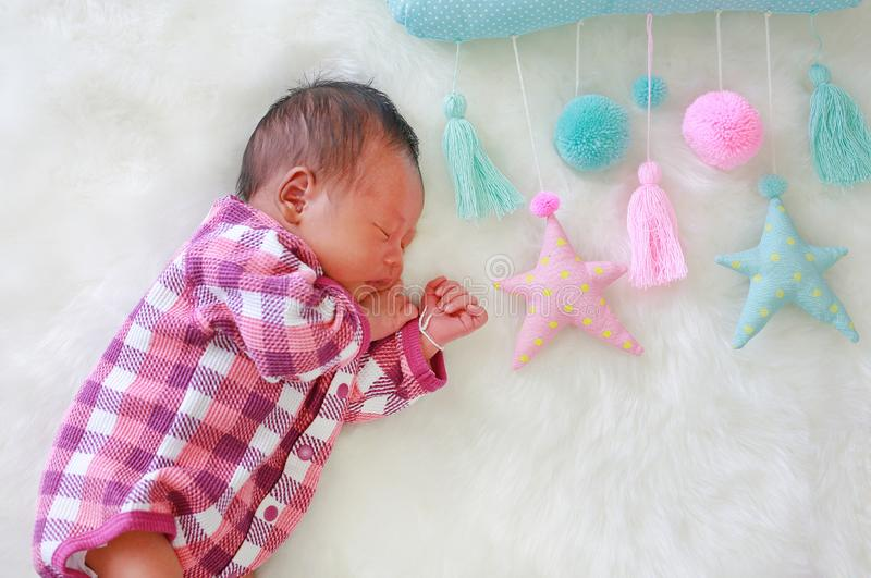 Portrait of sweet dreams newborn baby boy sleeping on white fur background with soft fabric mobile.  stock images