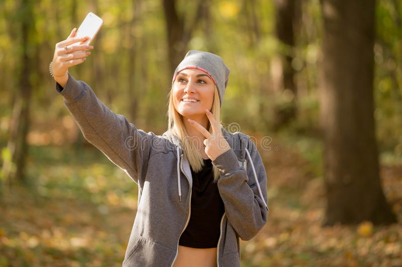 Cute girl makes selfie and shows two fingers stock image