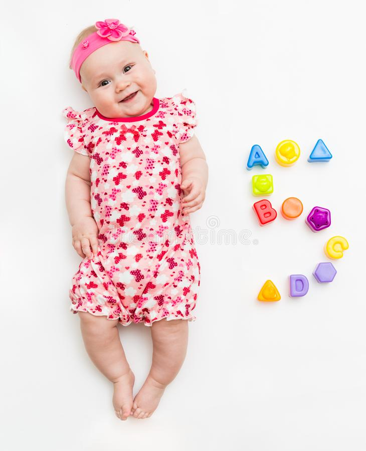Portrait of a sweet infant baby girl wearing a pink dress and headband bow, isolated on white in studio with number five stock photos