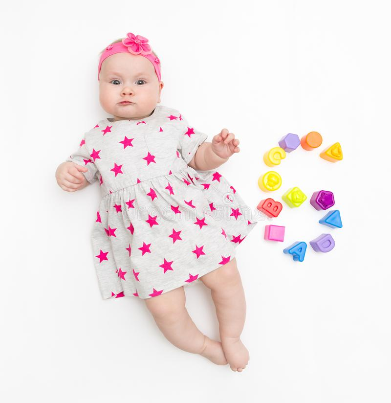 Portrait of a sweet infant baby girl wearing a pink dress and headband bow, isolated on white in studio with number six stock image