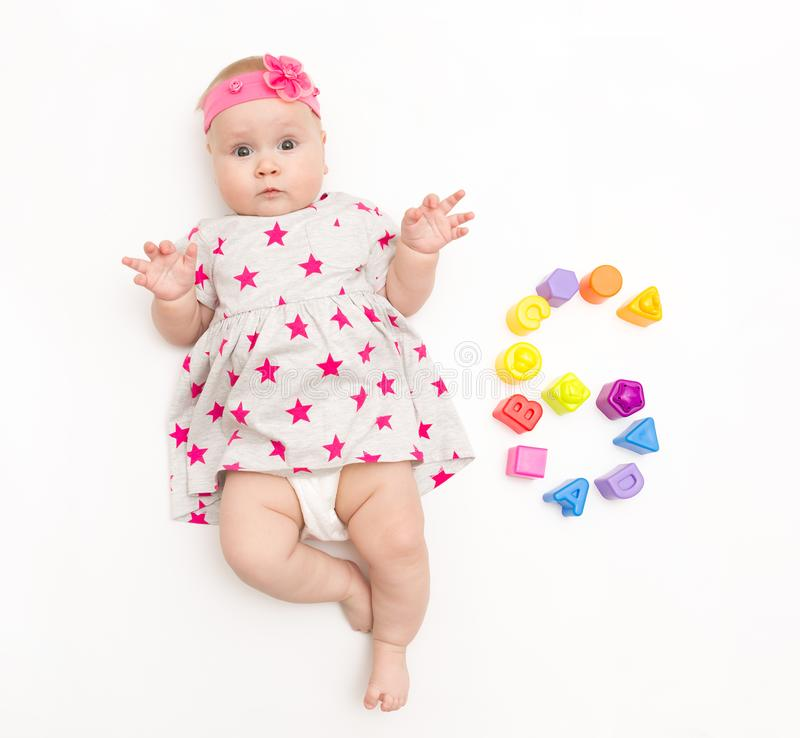 Portrait of a sweet infant baby girl wearing a pink dress and headband bow, isolated on white in studio with number six stock images