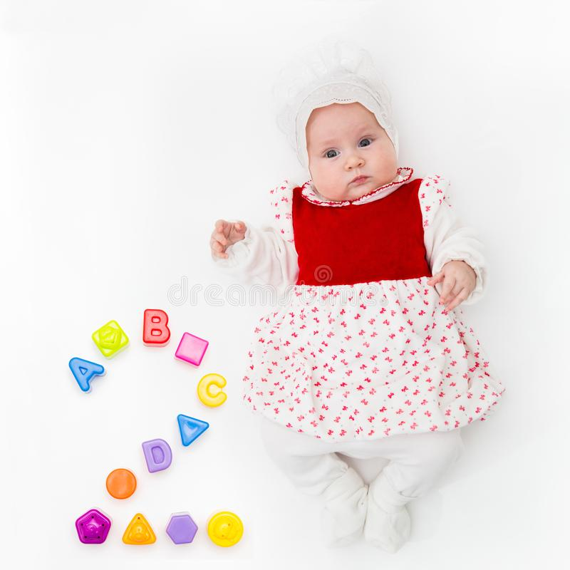 Portrait of a sweet infant baby girl wearing a red dress and bonnet,  on white in studio with number two from stock image