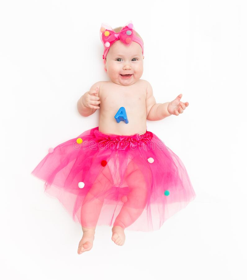 Portrait of a sweet infant wearing a pink tutu and headband bow, isolated on white in studio royalty free stock images