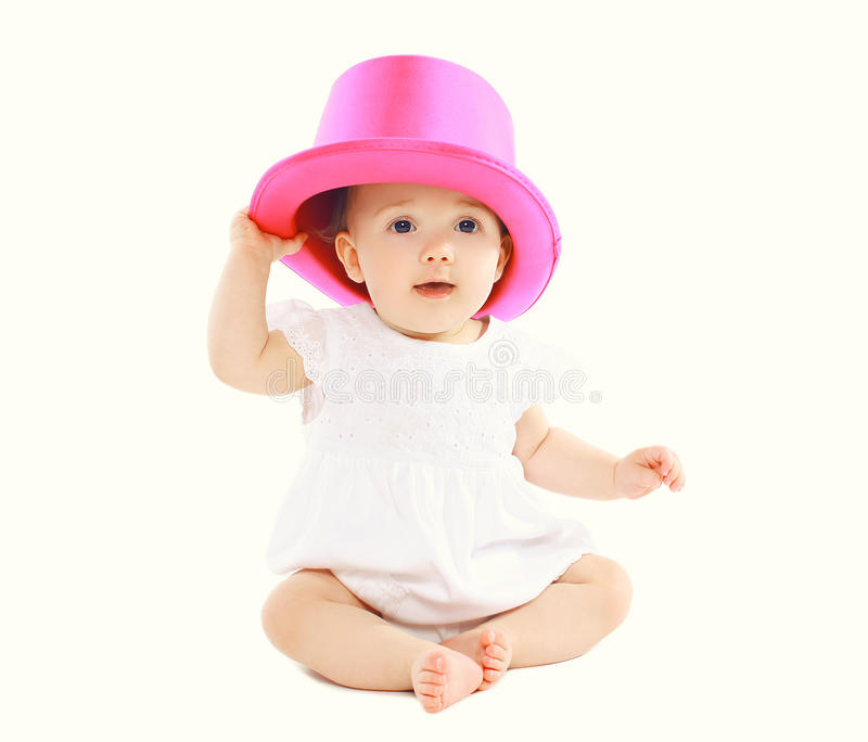 Portrait of sweet little baby sitting in pink hat. Portrait of sweet little baby sitting in the pink hat stock images