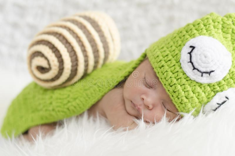 Portrait of sweet newborn baby in knitted snail costume stock images