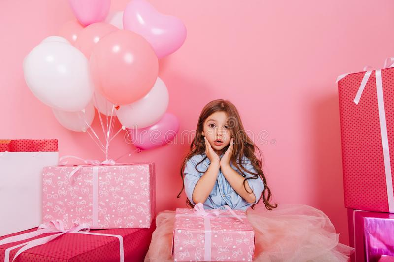 Portrait sweet surprised birthday kid looking to camera suround a lot of giftboxes, balloons  on pink background. Cute little girl with long brunette hair stock image