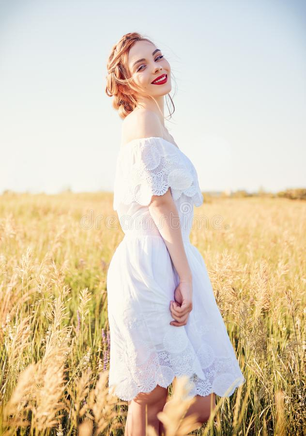 Portrait of sweet young smiling girl wearing white dress in meadow stock images
