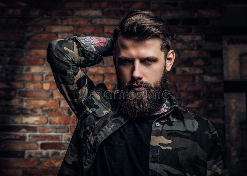 Portrait of a tattooed bearded guy in the military shirt. Studio photo against brick wall stock photo