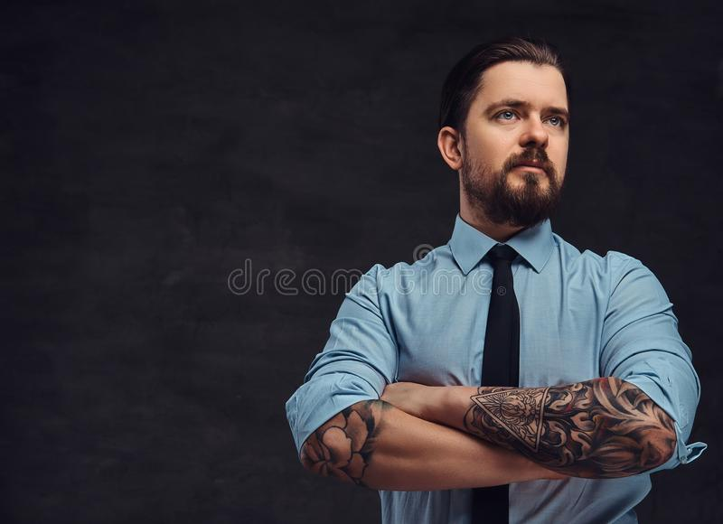 Portrait of a tattooed handsome middle-aged man with beard and hairstyle dressed in a blue shirt and tie, pose in a stock images