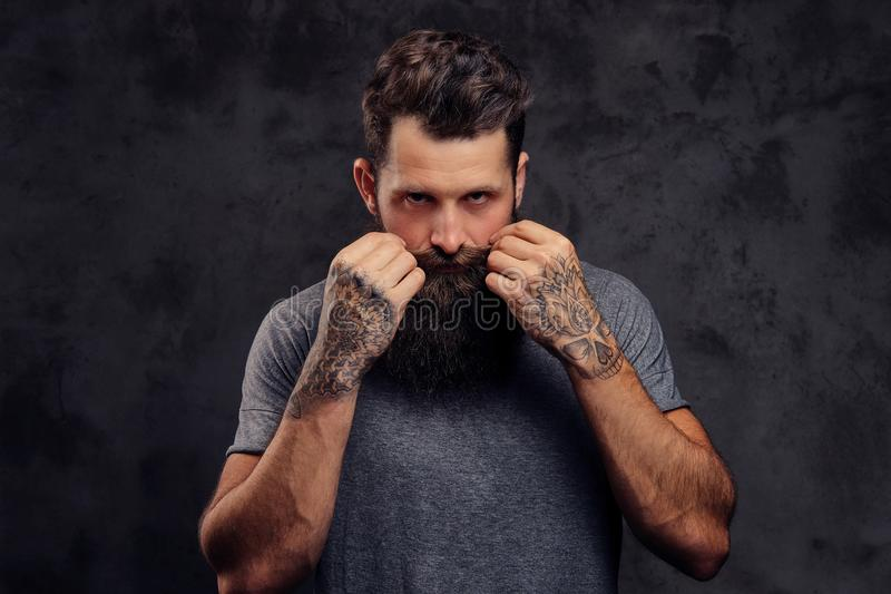Portrait of a hipster with full beard and stylish haircut, dressed in a gray t-shirt, stands with a thinking look in a stock photography