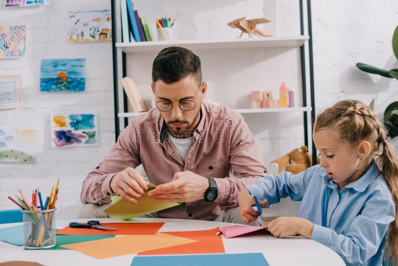 Portrait of teacher and cute preschooler cutting papers with scissors att able. In classroom stock image