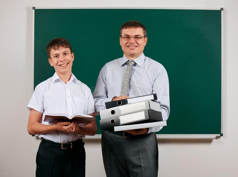 Portrait of a teacher dressed in business suit with folders, documents, posing with schoolboy at blackboard background - learning. And education concept stock photography