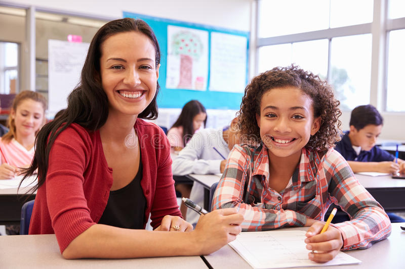 Portrait of teacher with elementary school girl at her desk royalty free stock image