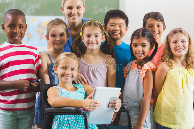 Portrait of teacher and kids in classroom stock images