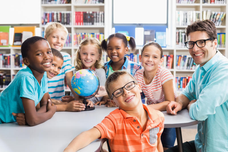 Portrait of teacher and kids in library stock photos