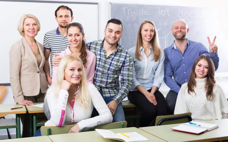 Portrait of teacher and students. Portrait of friendly teacher and adult students in classroom royalty free stock photo