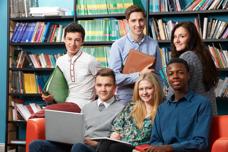 Portrait Of Teacher With Students In Library. Portrait Of Teacher And Students In Library royalty free stock photos