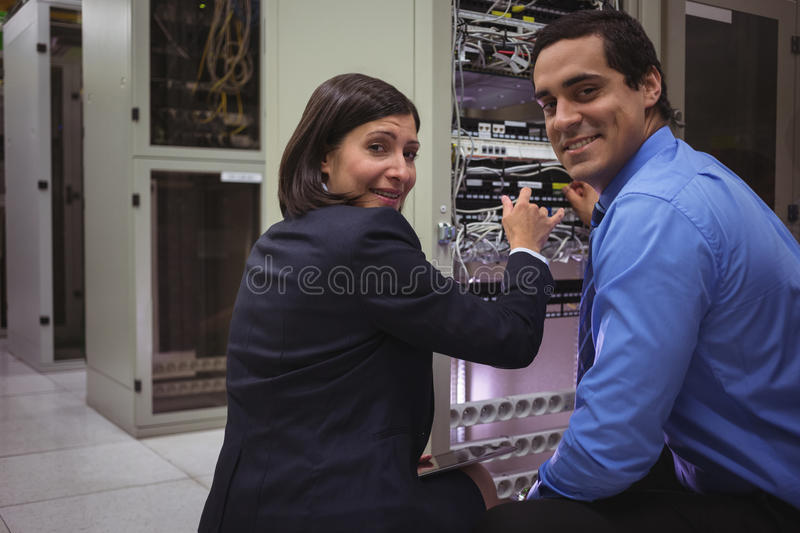 Portrait of technicians analyzing server. In server room stock photography