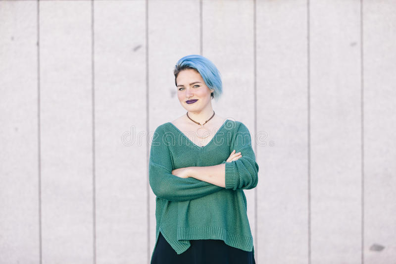 Portrait of a teen androgynous woman with blue dyed hair isolate. D on the street wearing a blue sweater stock images