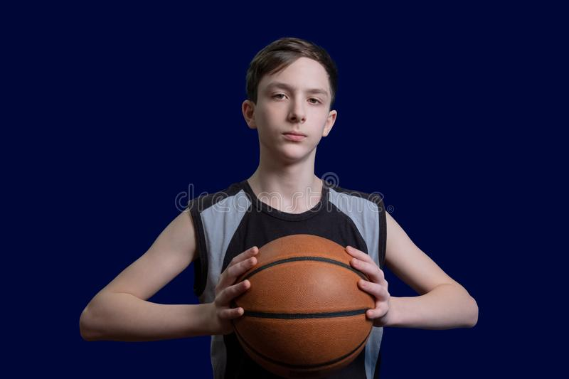 Portrait of a teen basketball player. The guy in the black t-shirt holds the ball in his hands. The concept of a sports poster or stock photography