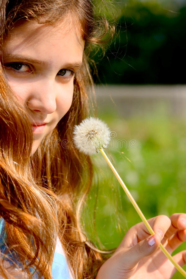 Portrait teen girl with dandelion