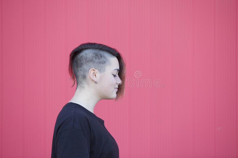 portrait of a teen androgynous lesbian woman on a pink wall stock photography