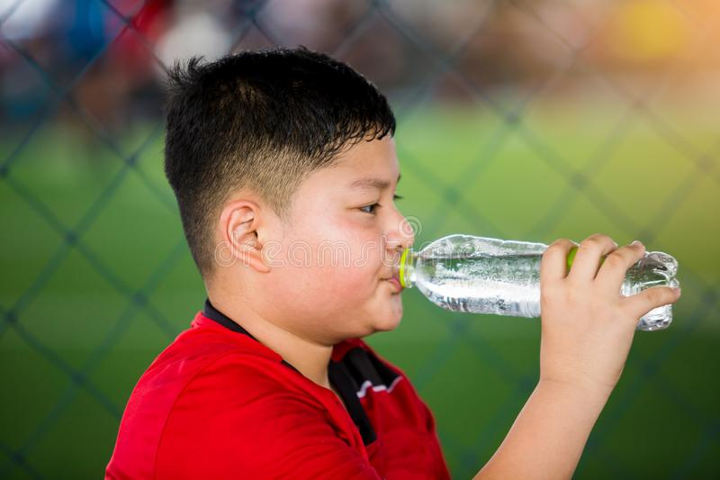 Portrait of teenage boy drinking water. At soccer field royalty free stock images