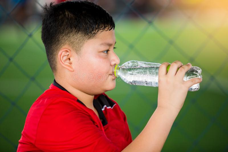 Portrait of teenage boy drinking water. At soccer field stock images
