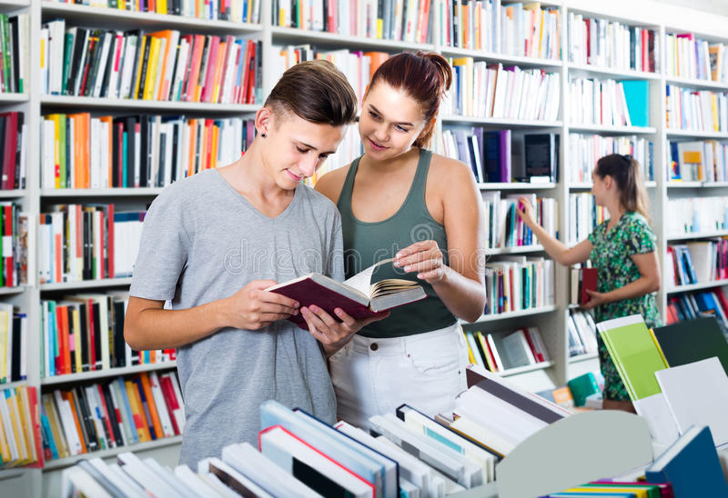 Portrait of teenage boy and girl customers looking at open book. Portrait of positive teenage boy and girl customers looking at open book standing among royalty free stock photography