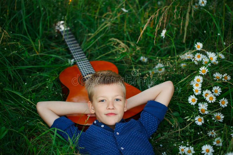 Portrait Teenage boy lying on grass with his acoustic guitar. stock photo