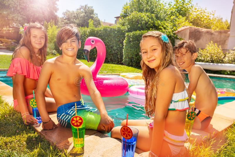 Friends with refreshing beverages by swimming pool stock photos
