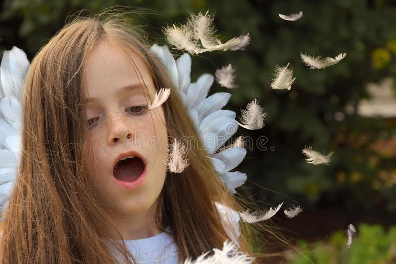 Teenage girl in angel costume blows flying feathers stock photo