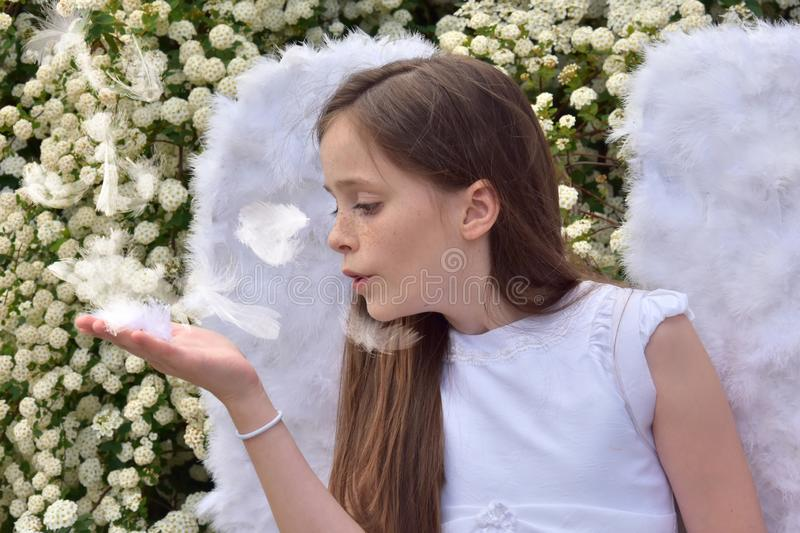 Teenage girl in angel costume catches flying feathers royalty free stock images