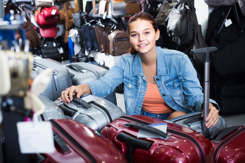 Portrait of teenage girl picking new big plastic luggage bag wit. Portrait of smiling american teenage girl picking new big plastic luggage bag with wheels in royalty free stock photo