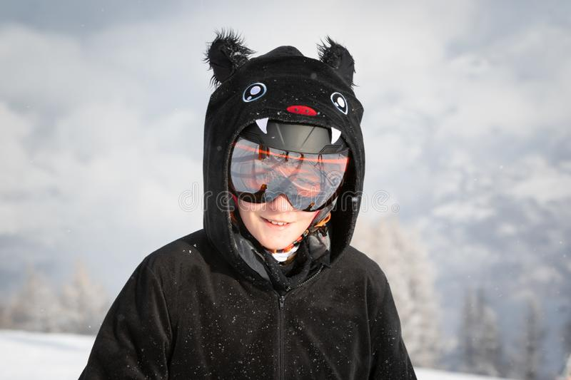 Portrait of a teenage girl wearing bat costume, helmet and looking at camera. Teenager enjoying skiing in Alps mountains. On a sunny day in light snowfall stock photos