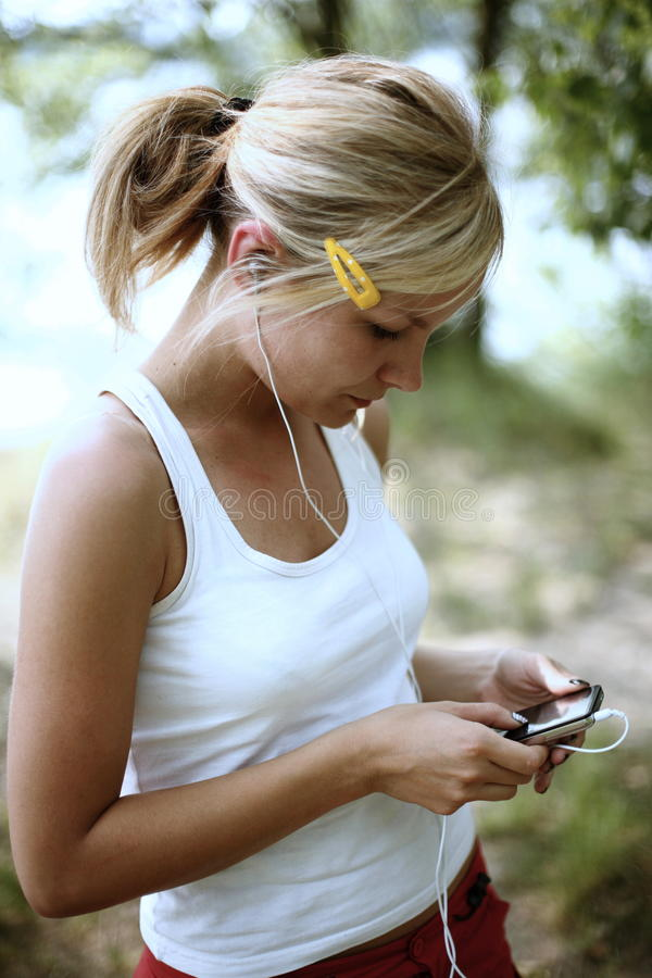 Portrait of a teenager. Wearing headphones and listening to music on her mp3 player royalty free stock images