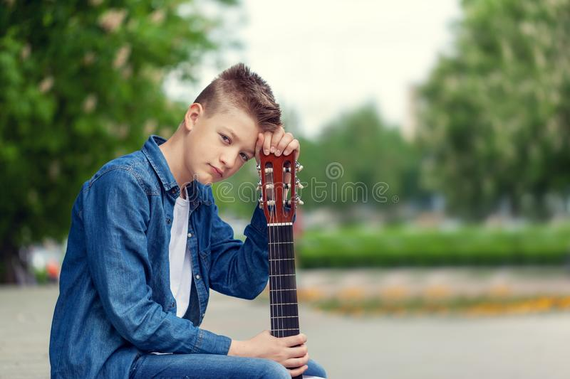 Portrait Teenager Boy with guitar sitting in the park royalty free stock images