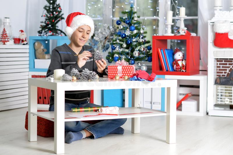 Portrait of teenager boy in Santa hat prepating for Christmas at home stock images